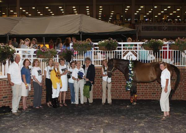 "Thoroughbred Retirement Foundation (TRF) at James River celebrating Multiple Choice in the Winner's Circle as ""Mr. TRF."" Pictured from left to right: Dr. Tom Newton; Robin Richards, Virginia breeder and national president of the Horsemen's Benevolent and Protective Association; Nancy Philpy; Deirdre Feeney; Chelsey Keiser, jockey who placed the wreath in honor of all racehorses; Robin Williams, former national president of TRF and founder of James River Chapter; Jennifer Ernst; Anne Tucker, president of James River chapter; Jeanna Bouzek, representing Colonial Downs; Ari Brothers; and Stephanie Nixon. Photo courtesy of Coady Photography"